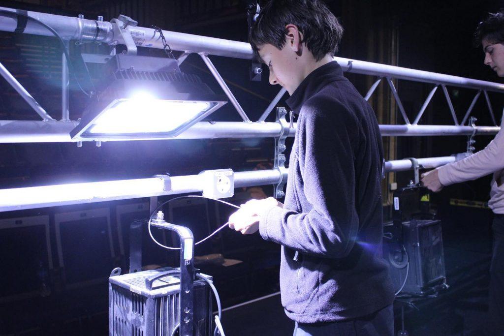 A member adjusts a light on the lighting rig