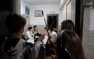A group of teenagers with camera equipment stand around some actors sat at a table