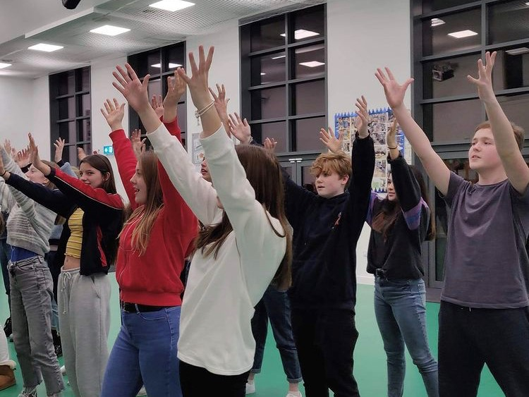 A group of teenagers stand with their hands in the air