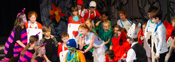 A group of children dressed in brightly coloured costumes pose at the end of a dance routine