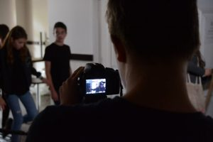 A teenager stands behind a camera facing towards a group of actors