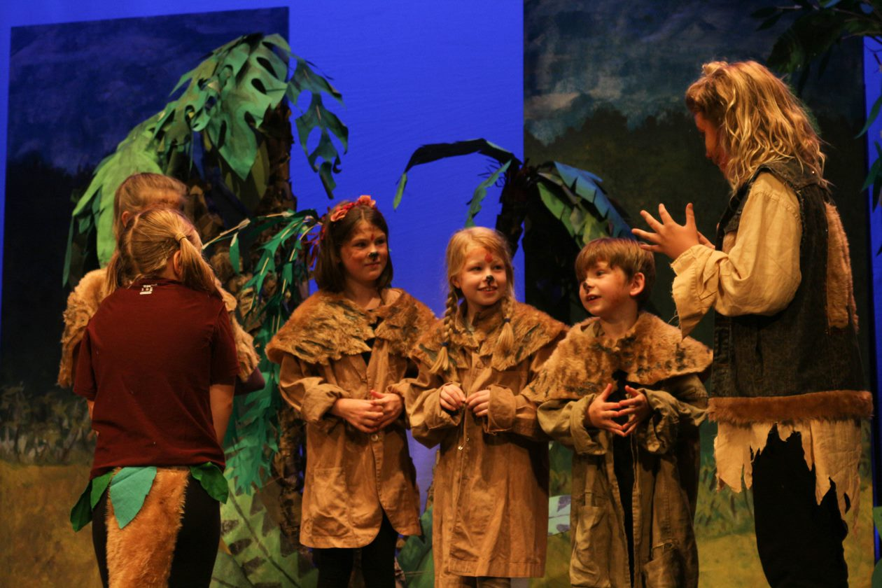 A group of children stand in front of palm leaves dressed as animals